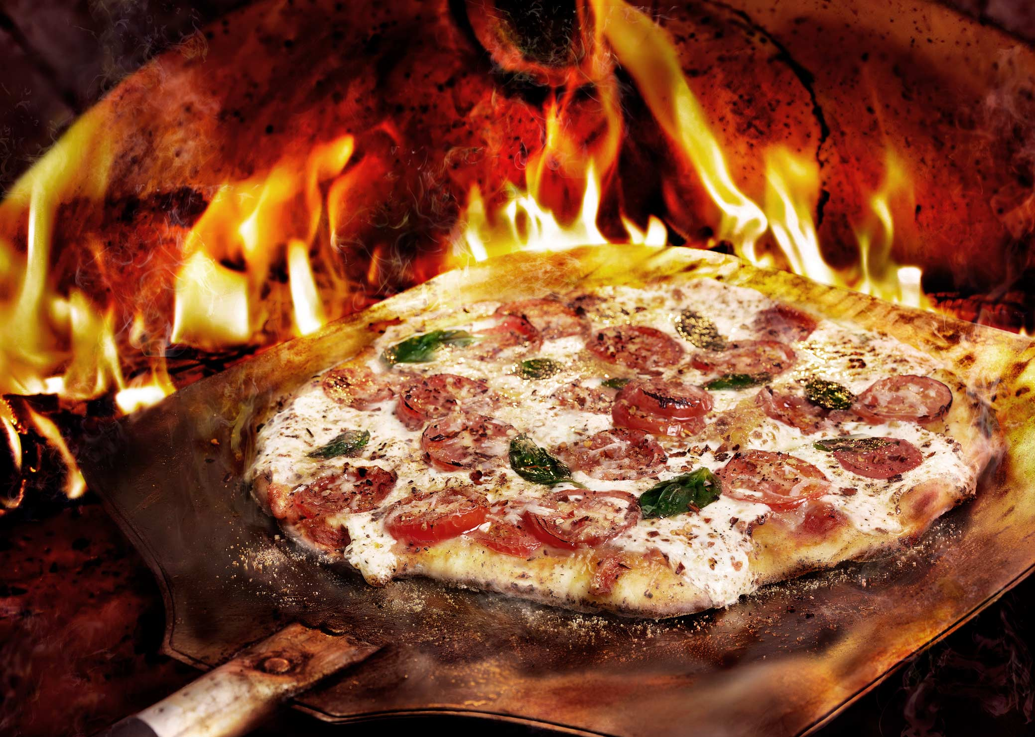 Hot Pizza Margherita in wood-fired oven with flames
