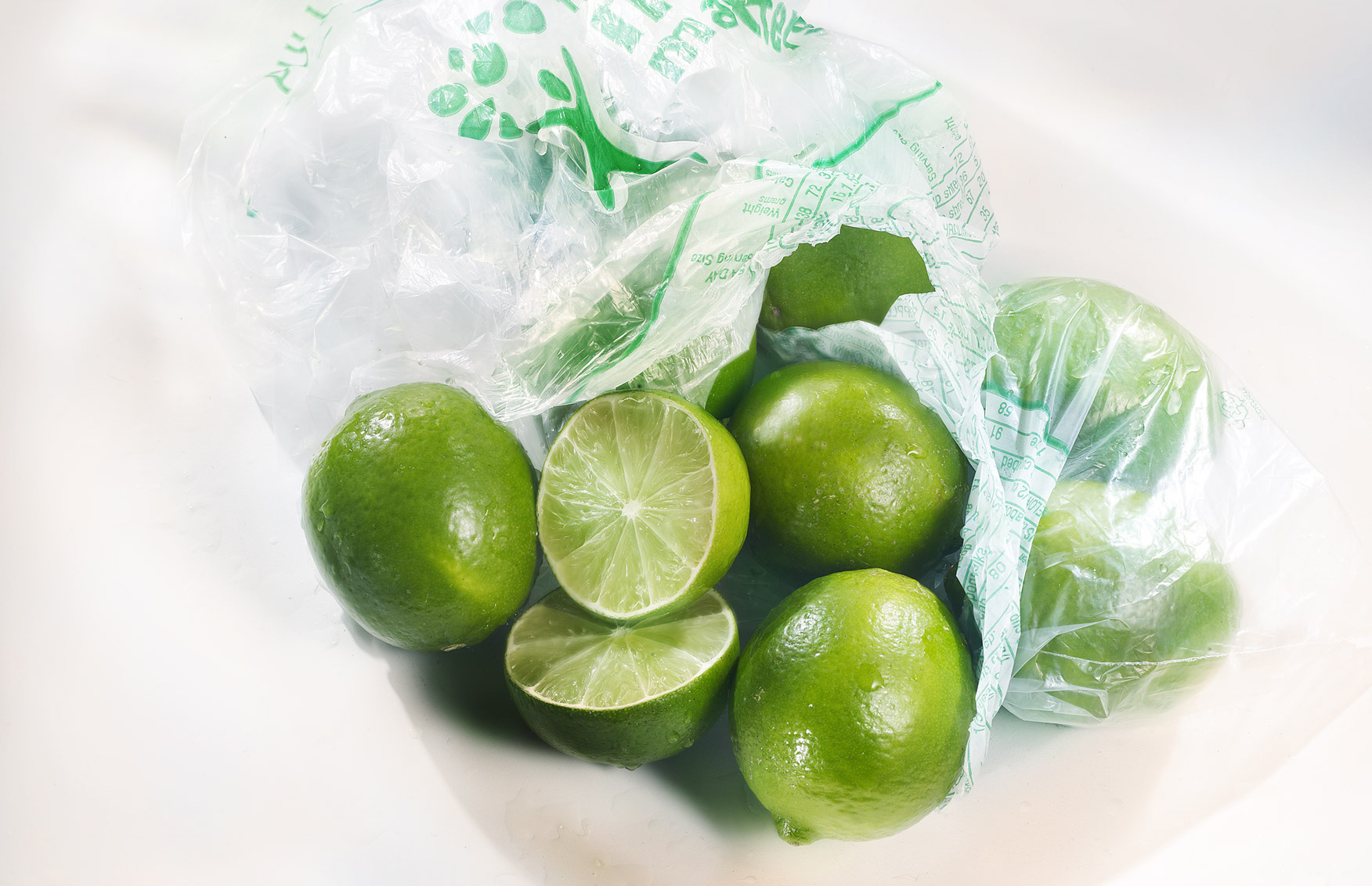 whole fresh green Limes in supermarket plastic bag with signature lighting