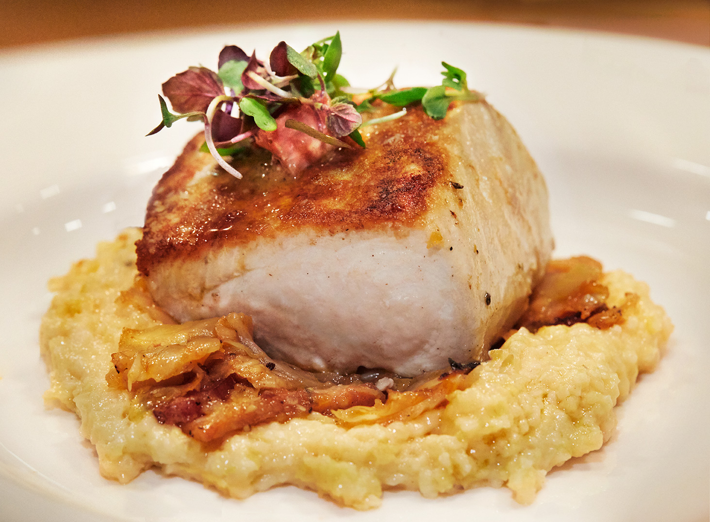 Pan Seared Hawaiian Wahoo fish with sweet potato grits, bacon braised cabbage and Tasso vinaigrette. Seafood, oysters and steak atThe Southern Steak and Oyster Restaurant in Nashville