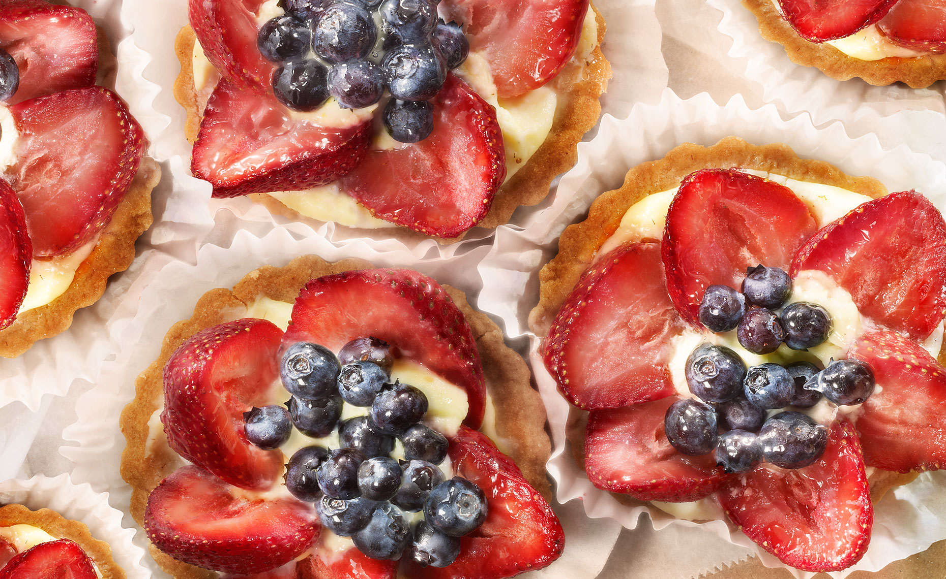group of strawberry and blueberry italian tarts on parchment paper