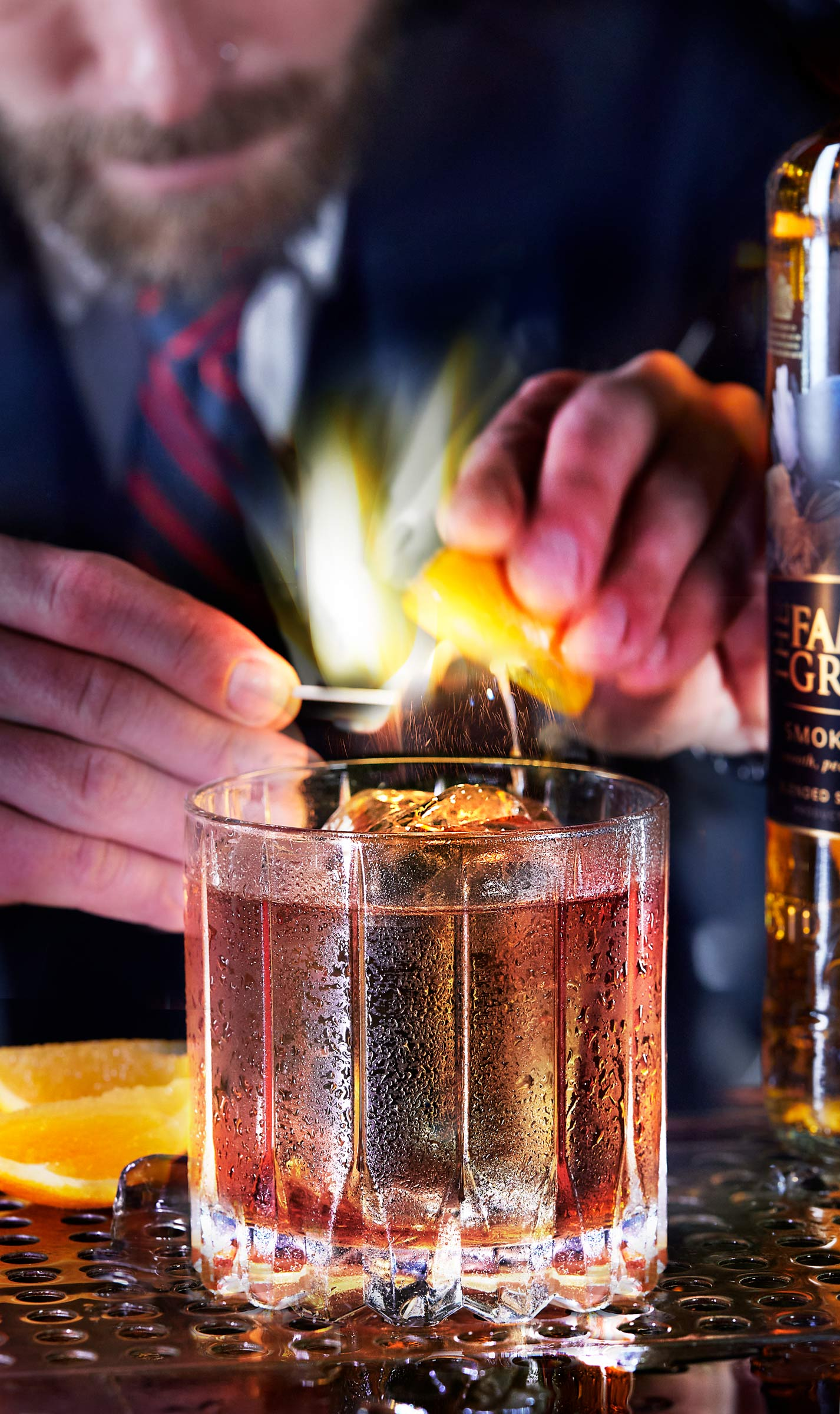 Smoky Bourbon with lemon twist on fire bartender